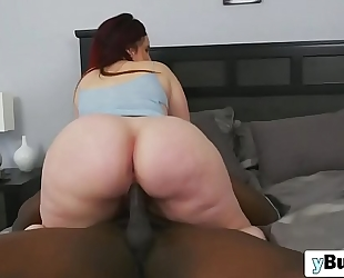 Chubby redhead floozy engulfing and riding biggest dark knob