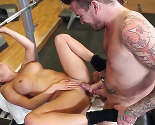 Horny slut with big juggs pleasuring tattooed guy in the gym