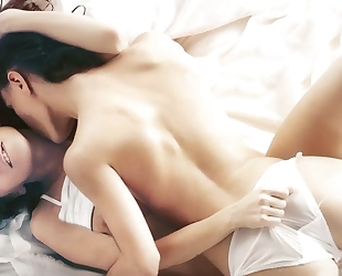 Two horny brunettes licking passionately in bed